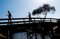 Two golfers walk across a bridge to the next hole in Amelia Island, FL