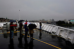 The Blackball Line ferry Coho arrives in Victoria, British Columbia in July rain.  Foot passengers wait to disembark.