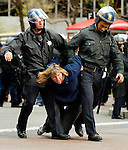 A protester struggles with police officers as she is arrested for blocking an intersection with about one hundred other demonstrators in protest against the war Iraq. The activists shut down the Financial District at Bush and Sansome/Market Street with nonviolent civil disobedience.