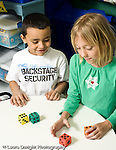 Education Elementary school Grade 1 mathematics manipulatives and hands on activities boy and girl counting dots on foam dice hands on learning vertical