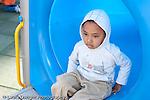 Education preschool outside at playground boy in blue plastic tube wearing hooded sweatshirt emotion mood sad depressed isolated horizontal