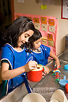 Education preschoool children ages 3-5 children playing at water table two girls playing separately vertical