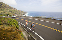 A couple of bicyclists (bicyclist) riding bicycles (bicycle) on Kalanianaole Highway on the windward coast of Oahu