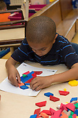 MR / Schenectady, NY. Zoller Elementary School (urban public school). Kindergarten inclusion classroom. Student (boy, 5, African American) does manipulative activity with pattern card and pattern blocks during math learning center time. MR: Ste14. ID: AM-gKw. © Ellen B. Senisi.