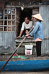 A man and his wife watch the action at the Cai Rang floating market, as a woman  stands in a boat next to their house on the Hau River, in the Mekong Delta, south of Can Tho, Vietnam. Sept. 30, 2011.