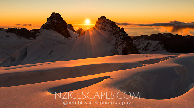 Sun sets over Tasman Sea on horizon and mountain ranges of Southern Alps with  crevasses in upper parts of Fox Glacier NEVE, Westland Tai Poutini National Park, West Coast, UNESCO World Heritage Area, New Zealand, NZ