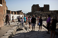 Tourists navigate ancient Roman roads on Friday, Sept. 18, 2015, in Pompeii, Italy. The city of Pompeii was destroyed when nearby Mount Vesuvius erupted on August 24, AD 79. The town and its residents were buried and forgotten until the ruins were discovered and eventually excavated hundreds of years later. The ruins are one of Italy's top tourist attractions today. (Photo by James Brosher)