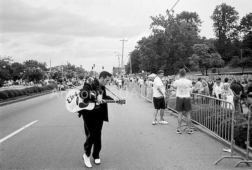 Memphis, Tennessee<br /> USA<br /> August 15, 2002<br /> <br /> A dancing Elvis impersonator on Elvis Presley Boulevard as some 50, 000 fans from around the world gather outside of Graceland for a candle vigil to mark the 25th anniversary of Elvis Presley's death.