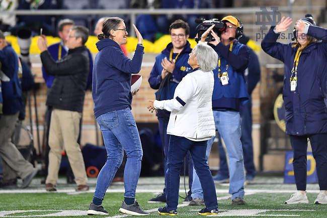 October 23, 2021; Meghan Sullivan, professor of philosophy and director of the Notre Dame Institute for Advanced Study, exchanges a high-five with Notre Dame Provost Marie Lynn Miranda after being recognized as a featured faculty member for the 2021 football season. (photo by Matt Cashore)