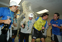 San Jose Earthquakes assistant coach Dominc Kinnear, is doused with water in the locker room after defeating the Chicago Fire 4-2 in the MLS Cup Championship, in Carson, Calif.