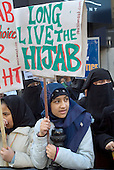 Young women protest outside the French Embassy in Knightsbridge, London, against the proposed ban on religious and political symbols in French state  schools, which would outlaw the wearing of the Muslim hijab.