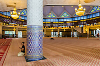 Worshiper Praying in the Prayer Hall of the Masjid Negara (National Mosque), Kuala Lumpur, Malaysia.