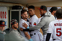 Rochester Red Wings Jake Cave (15) is held back by LaMonte Wade Jr. (4) and Jordany Valdespin as tempers flared in the dugout during an International League game against the Charlotte Knights on June 16, 2019 at Frontier Field in Rochester, New York.  Rochester defeated Charlotte 3-2 in the second game of a doubleheader.  (Mike Janes/Four Seam Images)