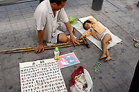 CHINA. Beijing. A man and his son begging for money in the Xidan shopping district in central Beijing. 2006.