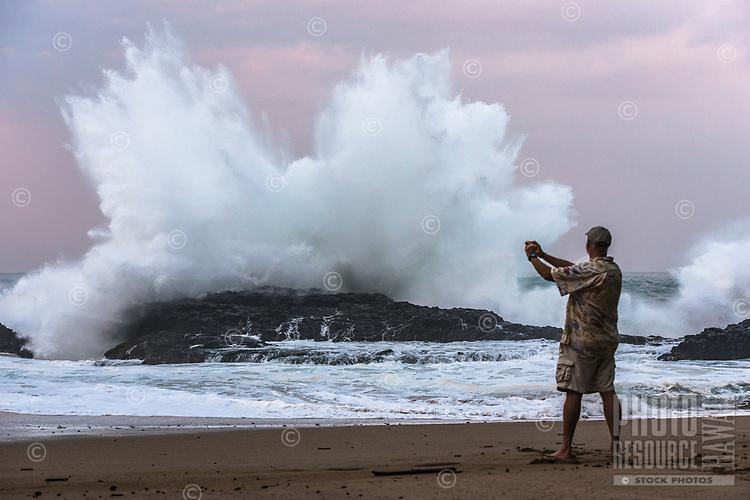 At twilight, a man takes a photo of a massive wave exploding onto the rocky shore at Lumahai Beach on Kaua'i.
