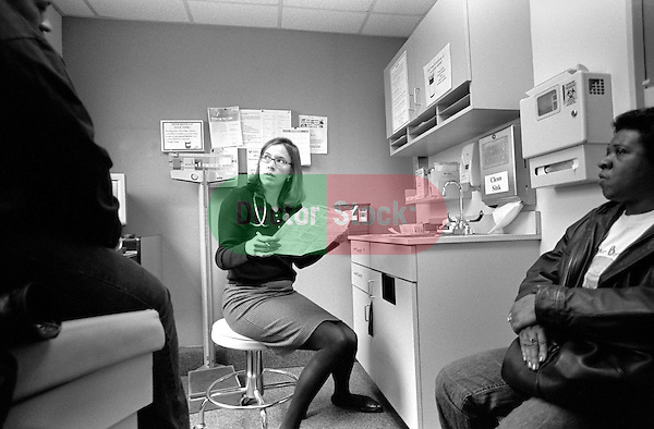 Young female internal medicine resident physician reading chart in examination room, middle age African-American female patient on examination table accompanied by seated middle-age African-American friend