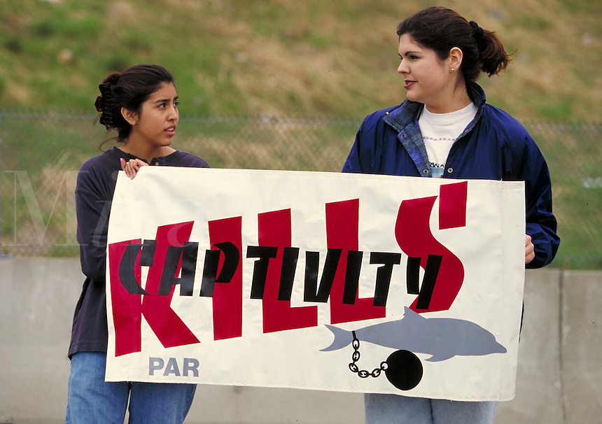 "Teen animal rights activists demonstrate against dolphin captivity; PMR, sign reads ""Captivity Kills"", animal rights, animal cruelty, protesters, demonstrators."