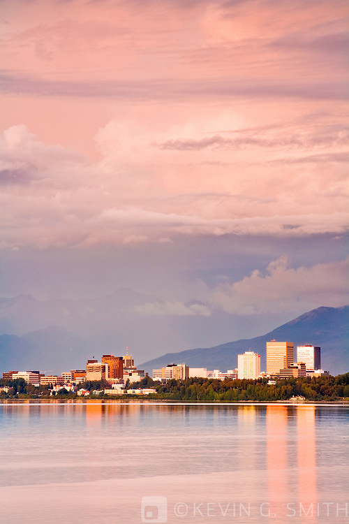 Anchorage skyline and the Chugach mountains at sunset, dramatic clouds, reflection in water, summer, shot from Earthquake Park