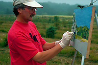 Man painting a landscape outdoors.