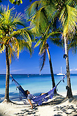 Negril, Jamaica. Tourist in blue hammock slung between two palm trees on a beach with blue-green sea behind.