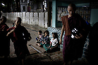 Novice monks collect food at a monastery on the outskirts of Mandalay, where some 2,300 monks live and study. A small group of children wait outside the monastery buildings for left over food that is handed out by the younger monks.
