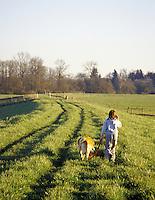Girl walking dog along Snohomish River dike, Snohomish, Washington