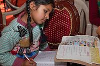 Dehradun, India.  Young Girl Studying in English-language Schoolbook.