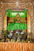 """Myanmar, Burma.  Buddha Shrine in the Nga Hpe Kyaung (Jumping Cat) Monastery, Inle Lake, Shan State.  The Buddha is in the Bhumisparsha Mudra position, """"calling the earth to witness"""" the Buddha's enlightenment.  The right arm hangs down over the right knee, palm inward, fingers down.  The left hand rests in the lap, palm upward."""