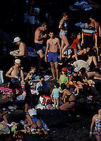 A crowd gathers on the black sand Karakum Beach.