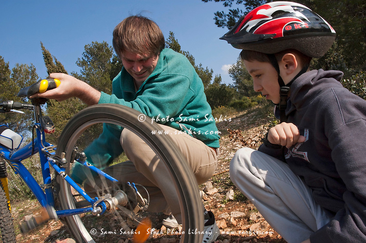 Father helping his son repair the flat tyre of his mountain bike.