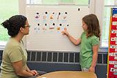 MR / Schenectady, NY. Zoller Elementary School (urban public school). Kindergarten classroom. Paraprofessional (Puerto Rican American) uses vocabulary cards to teach Spanish-language lesson. Girl, 5, native Spanish speaker. MR: Pac1, Cas12. ID: AM-gKw. © Ellen B. Senisi.