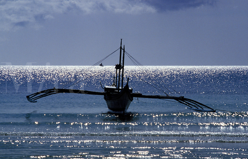 Philippines. Island of Boracay.  Traditional outrigger boat at the water's edge..