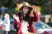 Brooke Mayer, member of the Homecoming Court at Fayetteville High School, waves to Trey Marley, communication projects manager with Fayetteville Public Schools, as he shoots video Friday, October 16, 2020 on the square in Fayetteville. The school district is making a video of the homecoming court for  viewing at the October 23rd football game. The school is not having it's annual homecoming parade or homecoming dance because of the covid-19 pandemic. Check out nwaonline.com/201017Daily/ and nwadg.com/photos for a photo gallery.(NWA Democrat-Gazette/David Gottschalk)