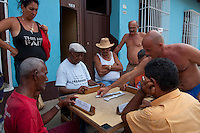 Men playing dominoes in the street with friends.