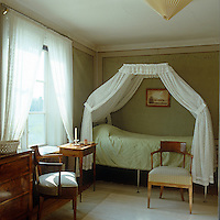 A guest room with Biedermeier furniture and an 18th century folding canopied campaign bed