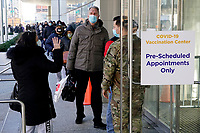 NEW YORK, NEW YORK - MARCH 02: A woman talks with a soldier at the Javits Center as people wait to receive a vaccine against the Coronavirus on March 2, 2021 in New York. Long wait times were reported at Manhattan's Javits Center vaccination with a long line of people extending outside and around the block. (Photo by Emaz/VIEWpress)