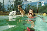 Boy and girl (7-9) playing in swimming pool, laughing, outdoors (Licence this image exclusively with Getty: http://www.gettyimages.com/detail/200387991-001 )