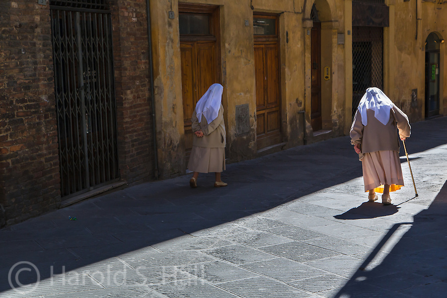 """Nuns are walking down the streets of Siena in the morning sun.  One is keeping to the 'Sunny Side of the Street""""."""