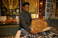 Sealer with a Mandala Thangka in is shop in Kathmandu. The lamas who paint thangkas use painting as a form of spiritual education and can spend up to 9 months on each canvas. Thangkas are seen hanging in every temple, monastery and family shrine in Tibet and Nepal.