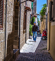 Urban Street Photography of the narrow streets of Rhodes, Greece the picture contains a red scooter and a man walking down the narrow streets of his city.