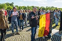 """Mehrere hundert Menschen versammelten sich nach einem anonymen Aufruf im Internet auf der Wiese vor dem Reichstagsgebaeude (Platz der Republik) um gegen die Einschraenkungen des oeffentlichen Lebens zur Eindaemmung der Covid-19-Pandemie zu protestieren. Unter ihnen viele Hooligans, Rechtsextreme, Anhaenger von Verschwoerungstheorien und Esoteriker. Sie riefen in Sprechchoeren """"Wir sind das Volk"""", """"Freiheit, Freiheit"""".<br /> Die Polizei versuchte, zunaechst erfolglos, die Menschen zum verlassen des Platzes zu bewegen. Ein Kamerateam der ARD wurde von einem Hooligan angegriffen. Dieser und andere aggressive Personen wurden festgenommen. Nach ca. 1 1/2 Stunden raeumte die Polizei den Platz.<br /> Links im Bild: Ein Mann haelt ein selbstgemaltes Schild gegen Zwangsimpfungen.<br /> Rechts im Bild: Ein Hooligan haelt eine Deutschlandfahne, auf der """"Fuck You NWO"""" steht. (NWO beudeutet """"Neue Weltordnung"""" und ist ein synonym fuer eine angebliche """"Juedische Weltverschwoerung"""".<br /> 6.5.2020, Berlin<br /> Copyright: Christian-Ditsch.de<br /> [NUR FUER REDAKTIONELLE ZWECKE! Werbung nur auf Anfrage beim Fotografen. Inhaltsveraendernde Manipulation des Fotos nur nach ausdruecklicher Genehmigung des Fotografen. Vereinbarungen ueber Abtretung von Persoenlichkeitsrechten/Model Release der abgebildeten Person/Personen liegen nicht vor. NO MODEL RELEASE! Don't publish without copyright Christian-Ditsch.de, Veroeffentlichung nur mit Fotografennennung, sowie gegen Honorar, MwSt. und Beleg. Konto: I N G - D i B a, IBAN DE58500105175400192269, BIC INGDDEFFXXX, Kontakt: post@christian-ditsch.de<br /> Bei der Bearbeitung der Dateiinformationen darf die Urheberkennzeichnung in den EXIF- und  IPTC-Daten nicht entfernt werden, diese sind in digitalen Medien nach §95c UrhG rechtlich geschuetzt. Der Urhebervermerk wird gemaess §13 UrhG verlangt.]"""