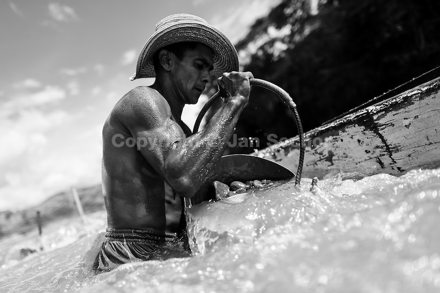 A Colombian sand miner unloads a bucket full of gravel into his boat anchored in the middle of the river La Vieja in Cartago, Colombia, 8 February 2013. Artisanal (unmechanised) sand mining is an ancient mining technique used to obtain sand for construction purposes. Depending on the natural conditions (strength of the stream, depth of the river etc.), together with the sand miners' physical condition, the material is extracted in metal buckets, either by standing on the river bottom and searching for sand by feet, or, diving up to 3-5 meters deep using a wooden plank with steps. In spite of the physically demanding work, a sand miner's daily salary does not exceed 15-20 US dollars. However, the sand miners are very proud of their profession, valuing their work freedom above all, and usually, as long as their health and strength permit, they keep facing the river stream.