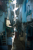 INDIEN Megacity Metropole Mumbai Bombay, Menschen leben in Huetten im Slum Dharavi, enge Gasse / INDIA Mumbai Bombay, Dharavi slum, huts of migrants and picture of Indira Gandhi