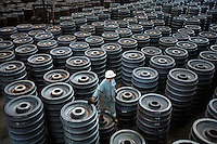 A worker inspects stacks of train wheels at the Wheel and Tyre Plant of Ma Steel (Maanshan Iron & Steel Co.) in Maanshan, Anhui Province, China. The plant is the largest producer of train wheels in China..10 Apr 2006