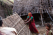 21 year old Asha Devi helps to lift the bamboo fence with her father in law while her 3 year old son, Gaurav Mandal (left) looks on in her house in Bhardaha in Saptari, Nepal.