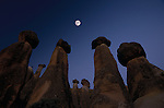 Full moon shines at dawn over tufa fairy chimneys, Cappadocia, Turkey.