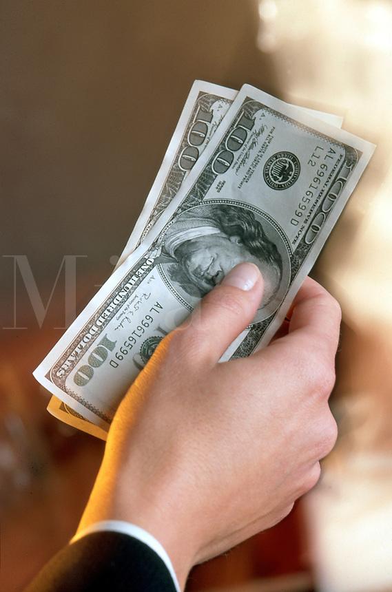 A businessman holding $100 bills.