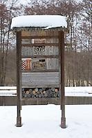 Insekten-Hotel, Insektenhotel im Winter bei Schnee, hohle Schilfstängel, Baumscheiben mit Bohrlöchern, Steine mit Bohrlöchern sowie ein Lehmangebot bieten Nistmöglichkeiten für Wildbienen, Mauerbienen und solitäre Wespen, Nisthilfe für Insekten