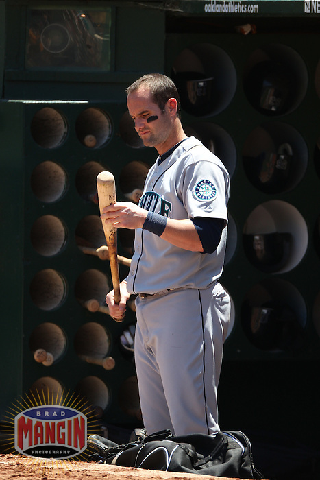 OAKLAND, CA - JULY 6:  Adam Kennedy #4 of the Seattle Mariners gets ready for his next at bat in the dugout against the Oakland Athletics during the game at the Oakland-Alameda County Coliseum on July 6, 2011 in Oakland, California. Photo by Brad Mangin