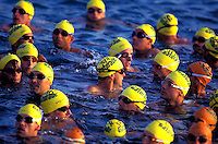 Closeup of men in yellow swimcaps surrounded by the blue ocean at the Ironman triathalon, Kona, Big island of Hawaii